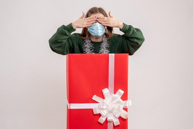 Vorderansicht junge frau in geschenkbox in maske