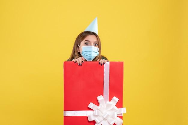 Vorderansicht junge frau in geschenkbox in steriler maske