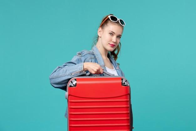 Vorderansicht junge frau in jeansjacke, die ihre rote tasche auf dem blauen raum hält