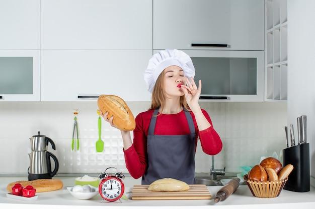 Vorderansicht junge frau in kochmütze und schürze mit brotbacken chefkuss in der küche