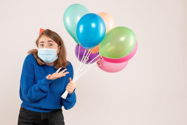 Vorderansicht junge frau in maske, die bunte luftballons hält