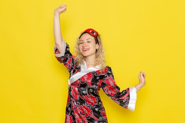 Vorderansicht junge frau in nachtgewand und tragende augenmaske, die sich darauf vorbereitet, auf gelbem schreibtisch nachtschlaf weibliche dunkle farbe zu schlafen