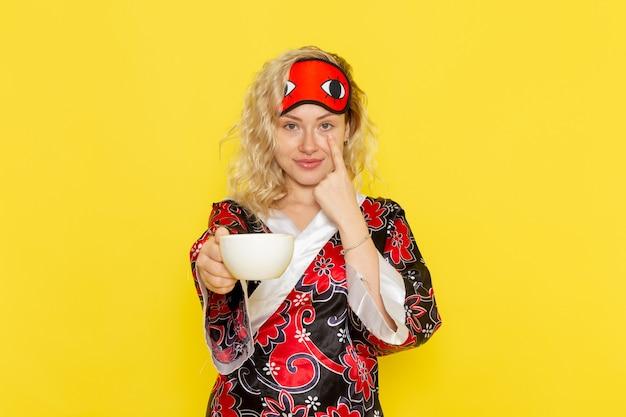 Vorderansicht junge frau in nachtgewand und tragende augenmaske, die sich darauf vorbereitet, tasse kaffee auf gelbem wandschlafmädchen-nachtbettmodell zu schlafen