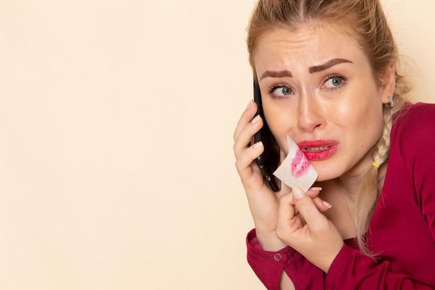 Vorderansicht junge frau in rotem hemd mit gebundenem mund, der am telefon auf dem cremefarbenen weiblichen stofffoto spricht