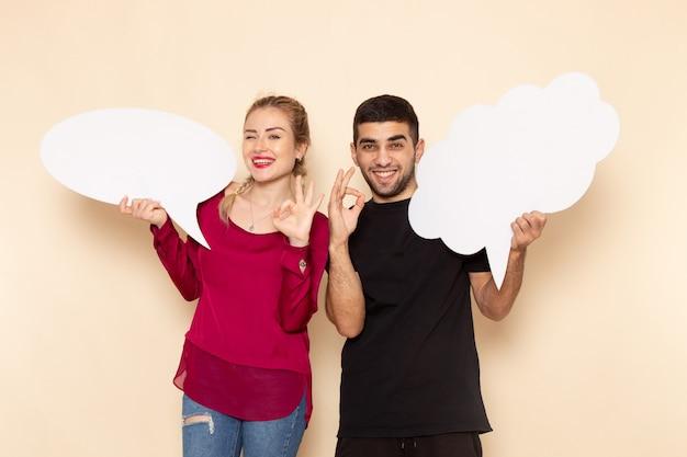 Vorderansicht junge frau in rotem hemd zusammen mit mann, der weiße zeichen auf dem cremeraum weiblicher stofffotogewalt hält