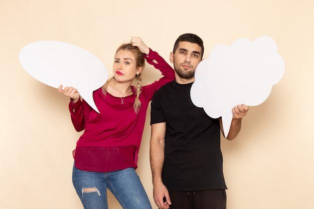 Vorderansicht junge frau in rotem hemd zusammen mit mann, der weiße zeichen auf dem cremeraum weibliches stofffoto hält