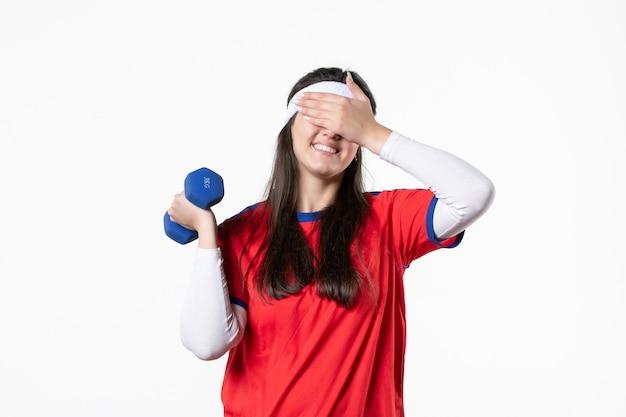 Vorderansicht junge frau in sportkleidung, die mit hanteln auf weißer wand arbeitet
