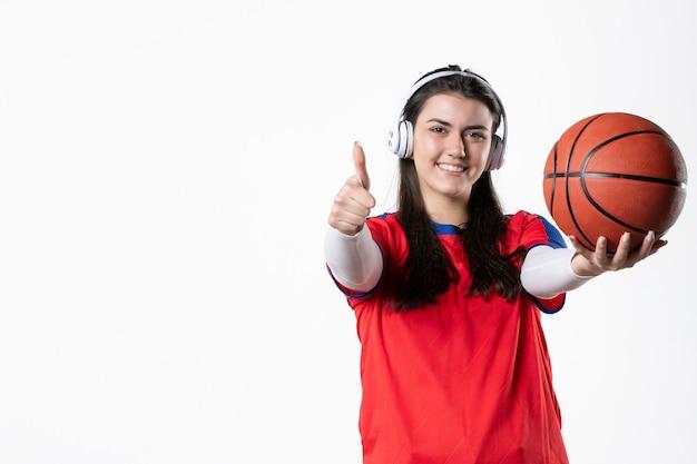 Vorderansicht junge frau in sportkleidung mit basketball weiße wand Premium Fotos
