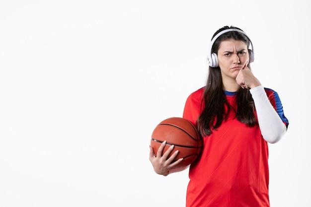 Vorderansicht junge frau in sportkleidung mit basketball weiße wand