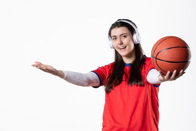 Vorderansicht junge frau in sportkleidung mit basketball
