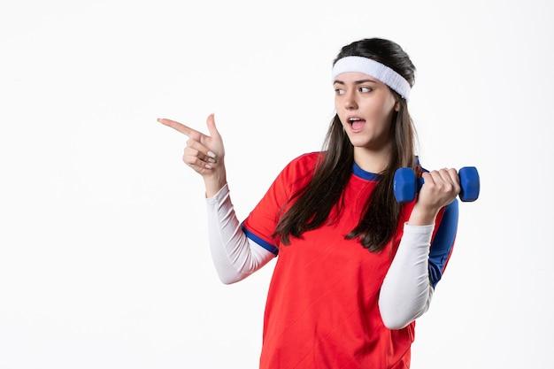 Vorderansicht junge frau in sportkleidung mit blauen hanteln auf weißer wand
