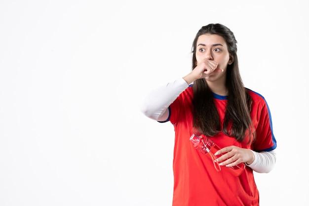 Vorderansicht junge frau in sportkleidung mit flasche wasser auf weißer wand