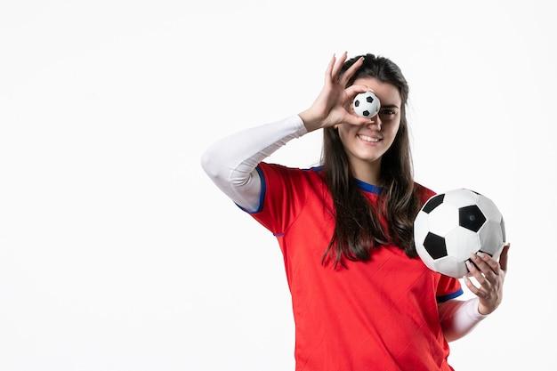 Vorderansicht junge frau in sportkleidung mit fußball auf weißer wand