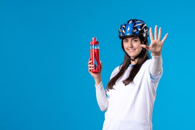 Vorderansicht junge frau in sportkleidung mit helm auf blauer wand