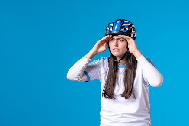 Vorderansicht junge frau in sportkleidung mit helm, der abstand auf blauer wand betrachtet