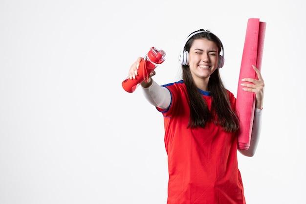 Vorderansicht junge frau in sportkleidung mit kopfhörern weiße wand