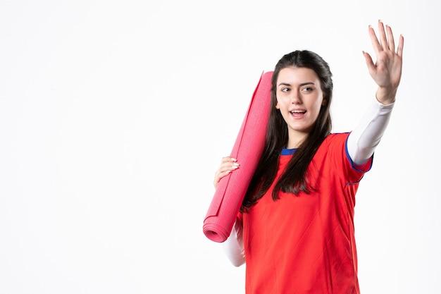 Vorderansicht junge frau in sportkleidung mit weißer wand der yogamatte
