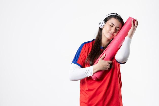 Vorderansicht junge frau in sportkleidung mit yogamatte, die musik weiße wand hört