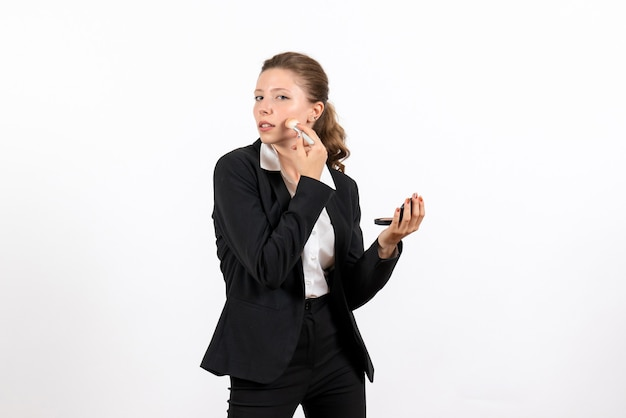 Vorderansicht junge frau in strengen klassischen anzug, die ihr make-up auf weißem hintergrund frau job ernstes kostümgeschäft macht