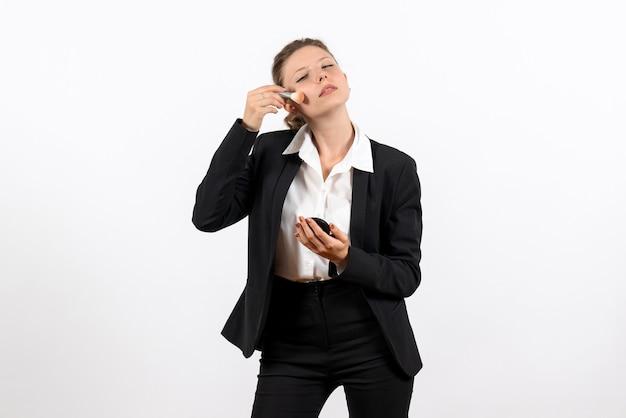 Vorderansicht junge frau in strengen klassischen anzug, die ihr make-up auf weißem hintergrund frau job kostüm geschäft weibliche arbeit macht