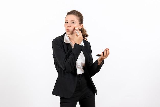 Vorderansicht junge frau in strengen klassischen anzug, die ihr make-up auf weißem hintergrund frau job kostümgeschäft ernst macht