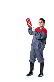 Vorderansicht junge frau in uniform, die verkaufsschild auf weißem hintergrund hält