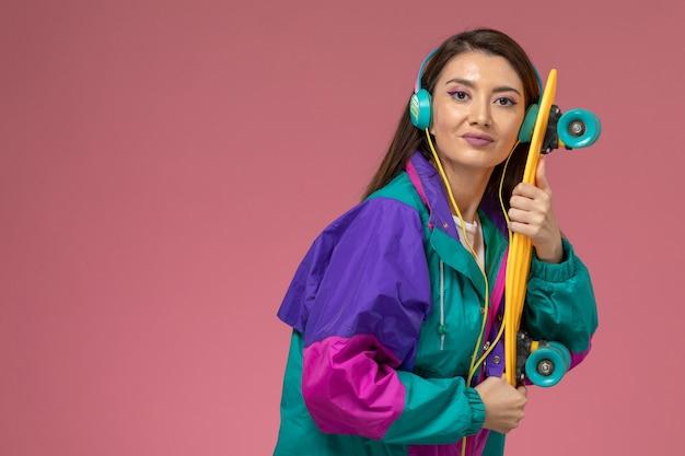 Vorderansicht junge frau in weißem hemd buntem mantel, der musik hört und skateboard hält, farbfrau-posenmodell