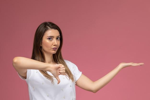 Vorderansicht junge frau in weißem hemd posiert zeigt im gegensatz zu zeichen auf der rosa wand, farbe frau pose modell frau