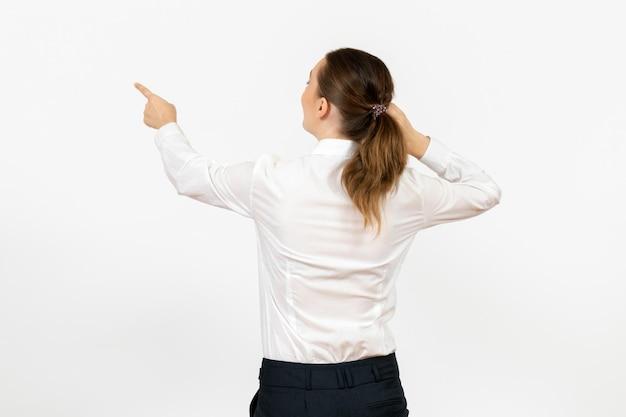 Vorderansicht junge frau in weißer bluse, die dem weißen hintergrund den rücken zuwendet