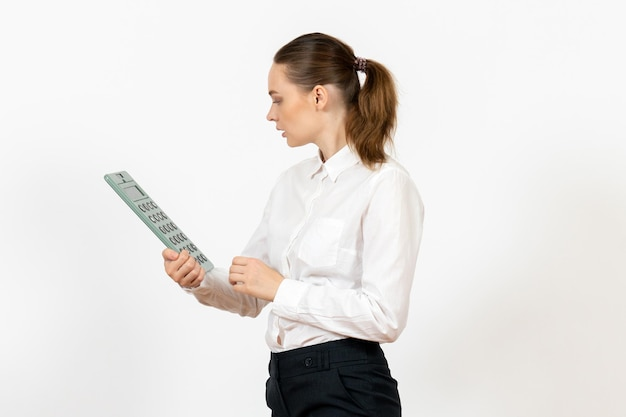 Vorderansicht junge frau in weißer bluse mit großem taschenrechner auf weißem hintergrund büro weibliche emotion gefühl job arbeiter weiß