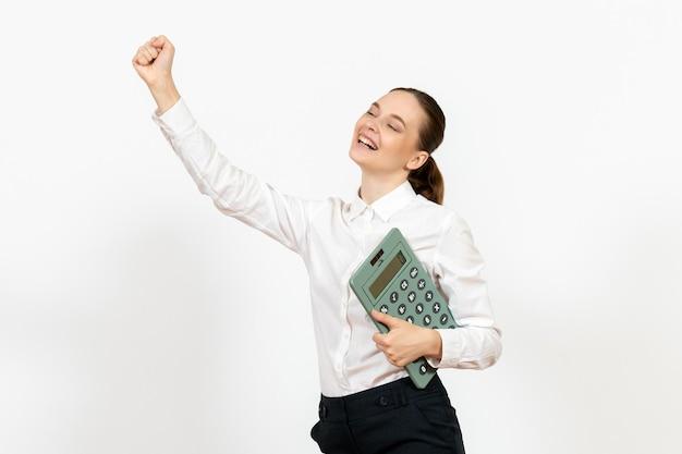 Vorderansicht junge frau in weißer bluse mit taschenrechner auf weißem hintergrund arbeiter weibliche emotion bürojob weiß