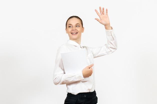 Vorderansicht junge frau in weißer bluse mit verschiedenen dokumenten auf weißem hintergrund weibliche emotion gefühl bürojob female