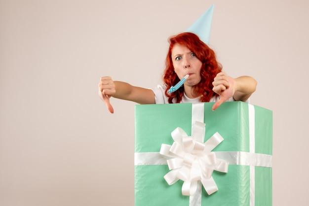 Vorderansicht junge frau innen geschenk mit kappe auf weißem hintergrund