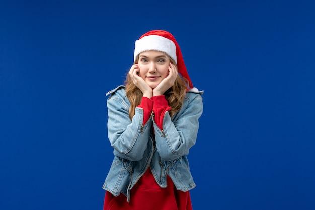 Vorderansicht junge frau lächelnd auf einem blauen hintergrund färben emotionsweihnachtsfeiertag