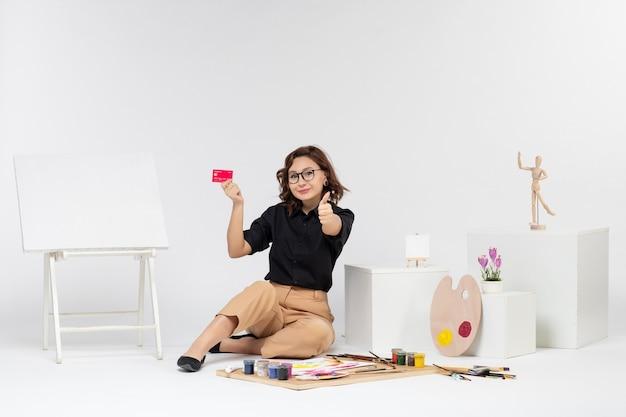 Vorderansicht junge frau mit bankkarte auf weißem hintergrund