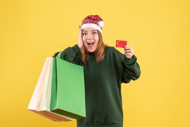 Vorderansicht junge frau mit bankkarte und einkaufspaketen