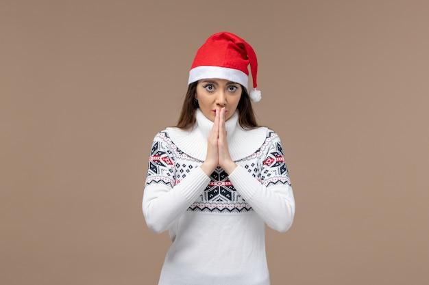 Vorderansicht junge frau mit betendem ausdruck auf dem braunen hintergrundweihnachtsgefühl neujahr