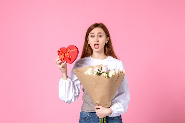 Vorderansicht junge frau mit blumen und geschenk als frauentag geschenk auf rosa hintergrund horizontalen märz frau datum gleichheit liebe sinnlich weiblich