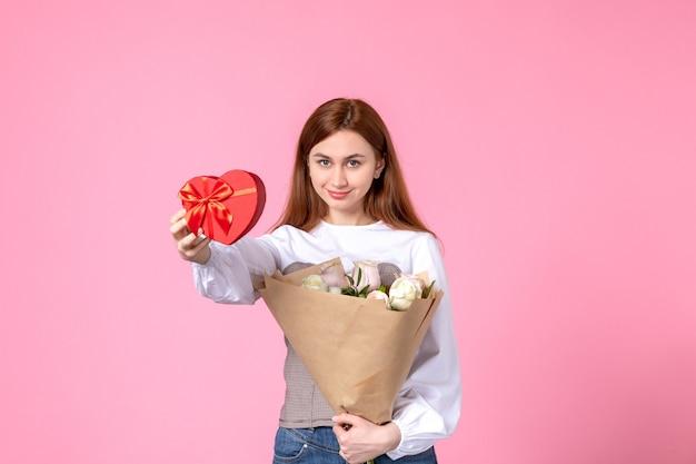 Vorderansicht junge frau mit blumen und geschenk als frauentagsgeschenk auf rosa hintergrund horizontale marschgleichheit liebe sinnliche weibliche datumsrose