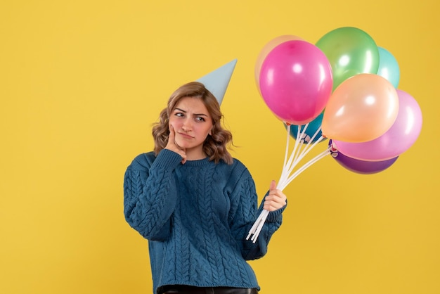 Vorderansicht junge frau mit bunten luftballons und denken