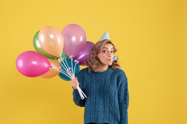 Vorderansicht junge frau mit bunten luftballons