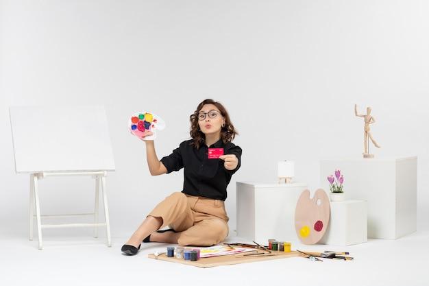 Vorderansicht junge frau mit farben und bankkarte auf weißem hintergrund
