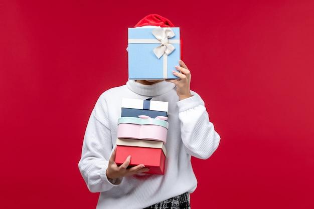 Vorderansicht junge frau mit feiertagsgeschenken auf einem roten hintergrund