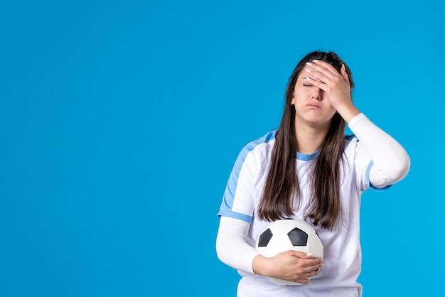 Vorderansicht junge frau mit fußball auf blauer wand