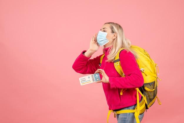 Vorderansicht junge frau mit gelbem rucksack, der ticket hält, das jemanden anruft
