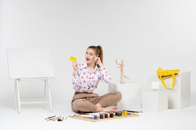 Vorderansicht junge frau mit gelber bankkarte und posiert auf weißem hintergrund