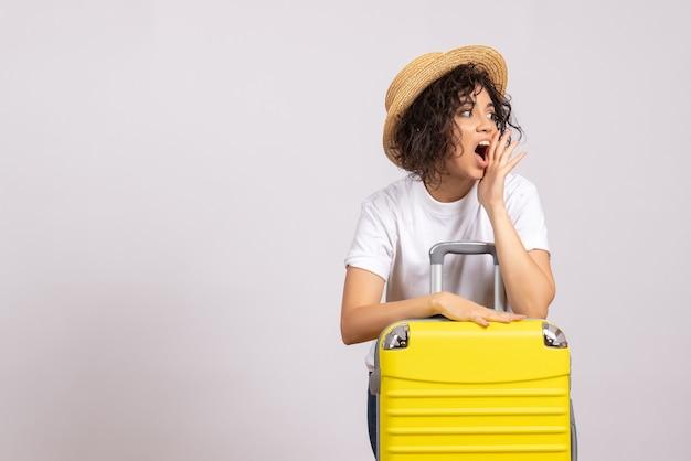 Vorderansicht junge frau mit gelber tasche, die sich auf die reise auf weißem hintergrund vorbereitet, sonnenfarbe reise urlaub flugzeug rest flug