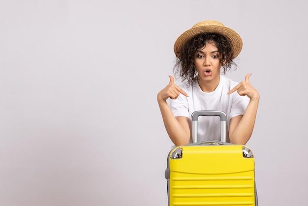Vorderansicht junge frau mit gelber tasche, die sich auf die reise auf weißem hintergrund vorbereitet, sonnenfarbe reise urlaub flugzeug rest tourist