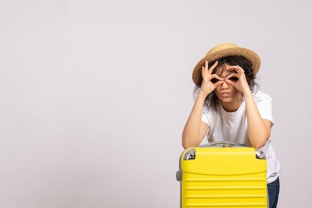 Vorderansicht junge frau mit gelber tasche, die sich auf die reise auf weißem hintergrund vorbereitet, sonnenfarbe reise urlaub flugzeug rest touristenflug