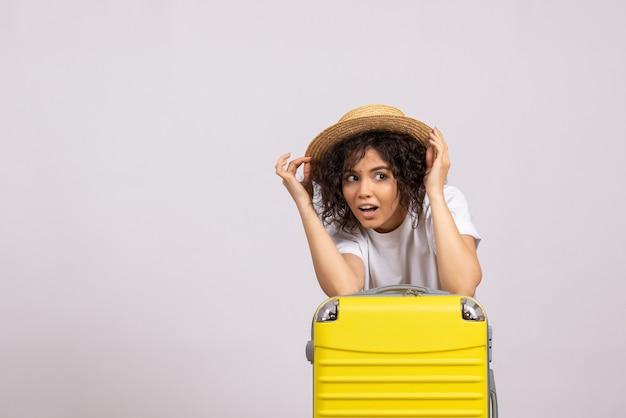 Vorderansicht junge frau mit gelber tasche, die sich auf die reise auf weißem hintergrund vorbereitet, urlaub flugzeug reise farben rest flug tourist